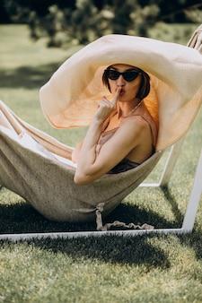 Beautiful woman lying in hammock wearing big sunhat