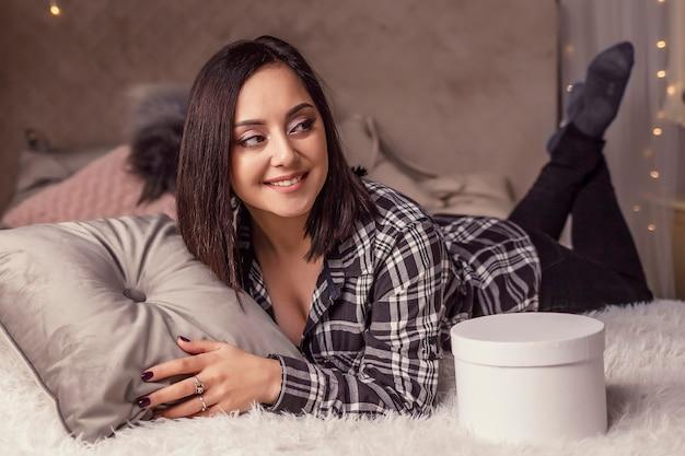 베개와 선물 상자를 들고 침대에 누워 쉬고 있는 아름다운 여성