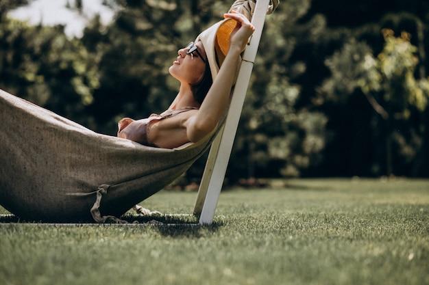Красивая женщина, лежа в гамаке, носить большой кепке