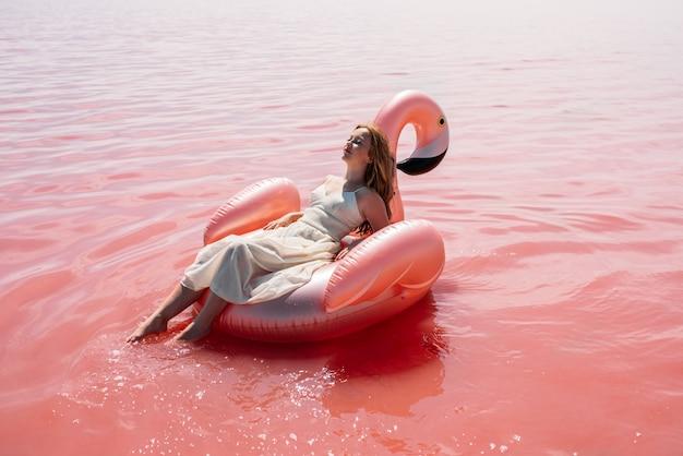 Beautiful woman lying on inflatable float mattress on pink sea