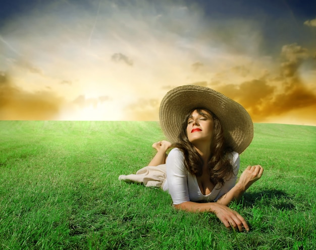 Beautiful woman lying n a field of grass