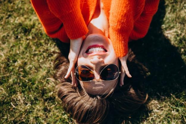 カラフルなセーターで草の上に横たわる美人