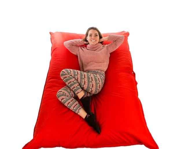 居間または白で隔離される他の部屋のための赤い正方形のビーンバッグソファに横たわっている美しい女性