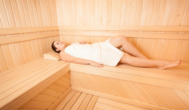 Beautiful woman lying with closed eyes on bench at sauna
