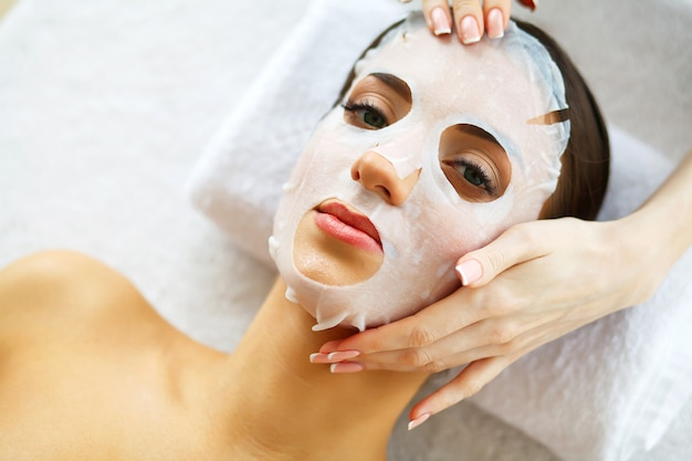 Beautiful woman lying with face mask.