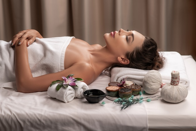 Beautiful woman lying with happy mood on vacation day. wellness body care and spa aromatheraphy concept.