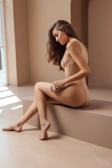 Красивая женщина делает массаж сухой щеткой