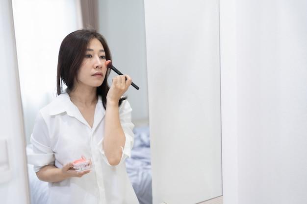 아름 다운 여자는 침실에서 메이크업, 메이크업 개념