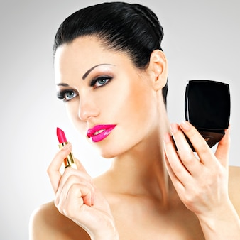 Beautiful woman makes makeup applying pink lipstick on lips.