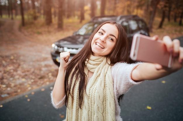 아름 다운 여자는 Selfie를 만든다. 소녀는 스마트 폰을 사용하고 있습니다. 손을 닫습니다. 가을 개념. 자동차로 가을 숲 여행. 프리미엄 사진