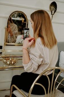 美しい女性は彼女のドレッシングテーブルの近くの彼女の部屋で自分撮りをします