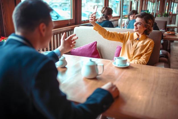 美しい女性はスーツを着た男に対して携帯電話のカメラでselfieを作る
