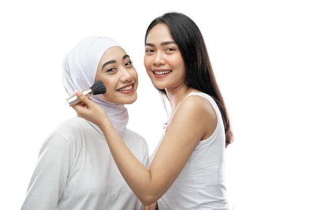 Beautiful woman makeup artist applying cheek with brush of young asian muslim woman in veil
