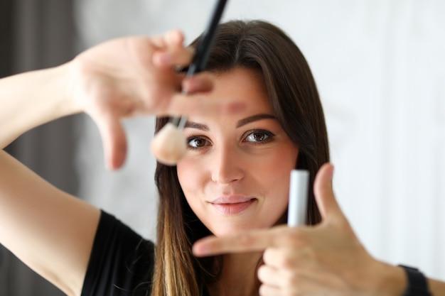 Красивая женщина-визажист предлагает сделать макияж для фотосессии замаскировать недостатки кожи