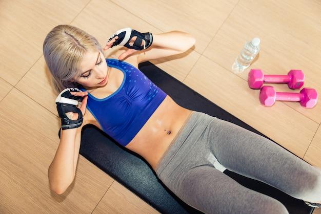 床にabsトレーニングを作る美しい女性