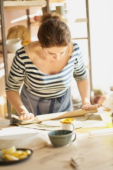 Beautiful woman making ceramic ware in workplace in sun light. concept for woman