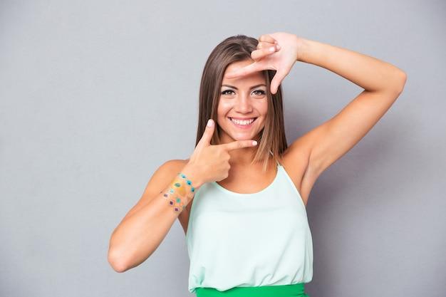 Красивая женщина, делая жест рамки пальцами