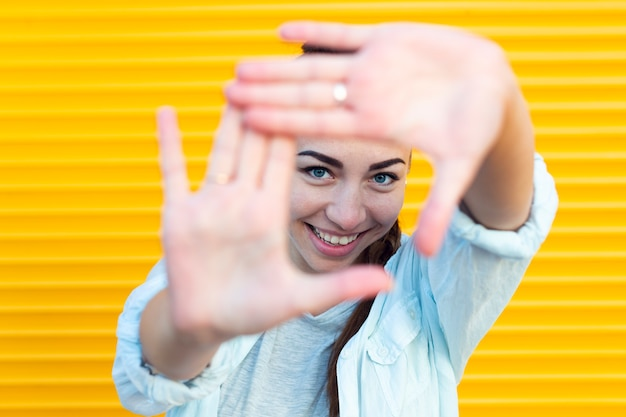 Beautiful woman making a frame with her hands while looking at the camera