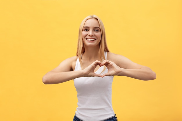 Beautiful woman making heart shape sign against a yellow background