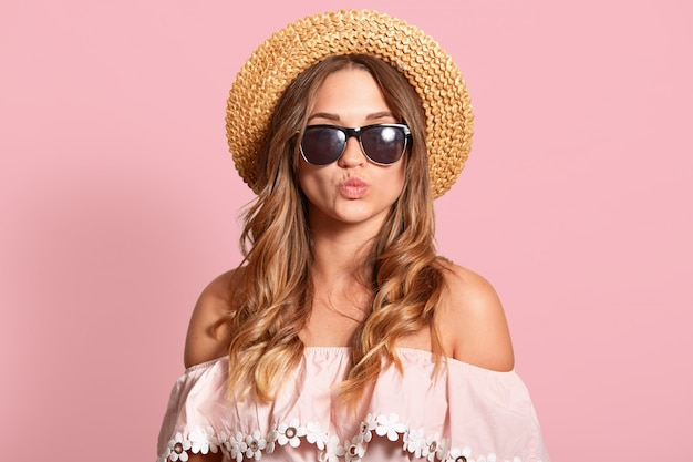 Beautiful woman making kissing gesture, keeps lips rounded, attractive female wearing summer outfit and dark sunglasses, posing isolated over rose studio wall with copy space for advertisement.