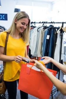 Красивая женщина делает оплату через кредитные карты при совершении покупок