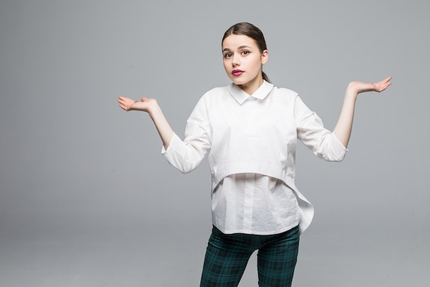Beautiful woman making a scale with her arms wide open, isolated in a white wall
