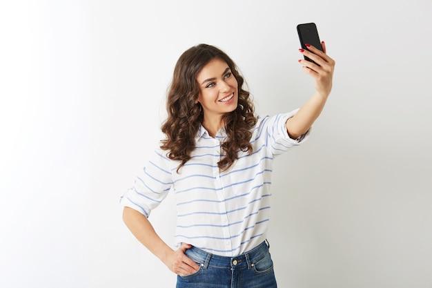 Красивая женщина делает селфи фото на мобильном телефоне, улыбается, счастлива, islolated, вьющиеся волосы, позитивное настроение, смотрит в камеру, привлекательная модель позирует