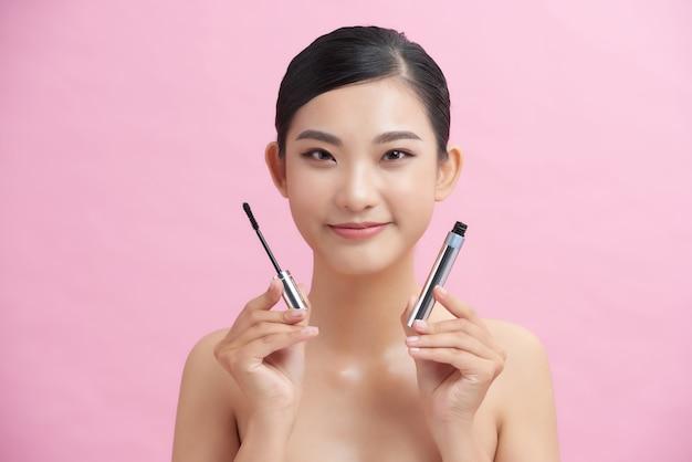 ピンクの背景にメイクの自然な肖像画の美しさの概念を適用する美しい女性のマスカラ