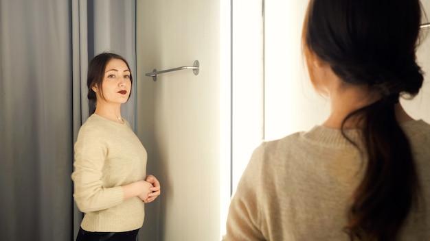 아름 다운 여자는 탈의실에서 옷을 측정합니다.