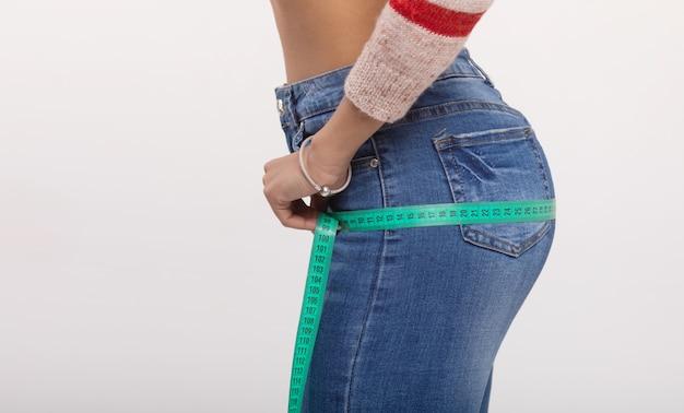 그녀의 엉덩이 측정하는 아름 다운 여자. 흰 벽에 고립 된 체중 감량 개념입니다.