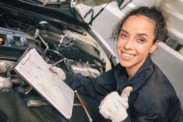 제복을 입은 아름다운 여성 역학은 해제 된 차량 및 종이보고와 함께 자동 서비스에서 일하고 있습니다.