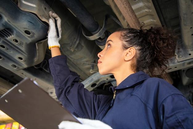 제복을 입은 아름다운 여성 역학은 해제 된 차량 및보고와 함께 자동 서비스에서 일하고 있습니다.
