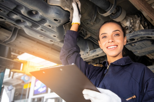 Beautiful woman mechanics in uniform is working in auto service with lifted vehicle and reporting.