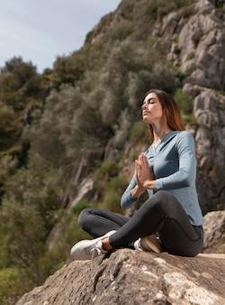 屋外で瞑想する美しい女性