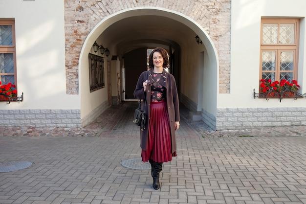 Красивая женщина среднего возраста, идущая по улице в солнечный осенний или весенний день.