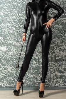 Beautiful woman mistress in latex bodysuit stands near wall holding a whip