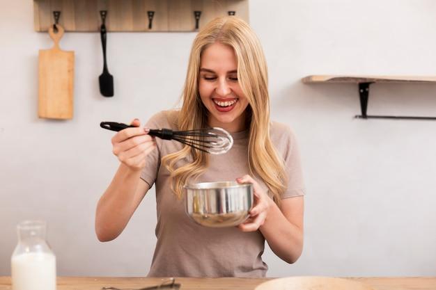 Beautiful woman mixing the eggs in the metallic bowl