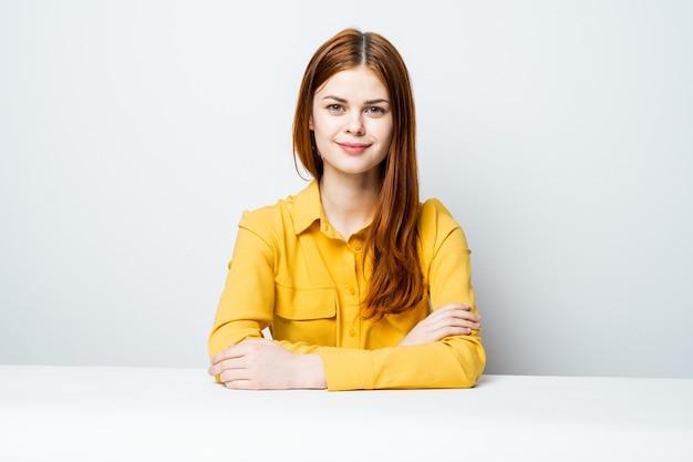 黄色のシャツのテーブルで美しい女性モデルはさまざまな感情をもたらす