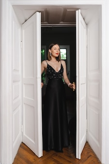 Bellissima modella vestita con un elegante abito lungo nero in una posa alla moda in un interno moderno con porta bianca su muro bordeaux