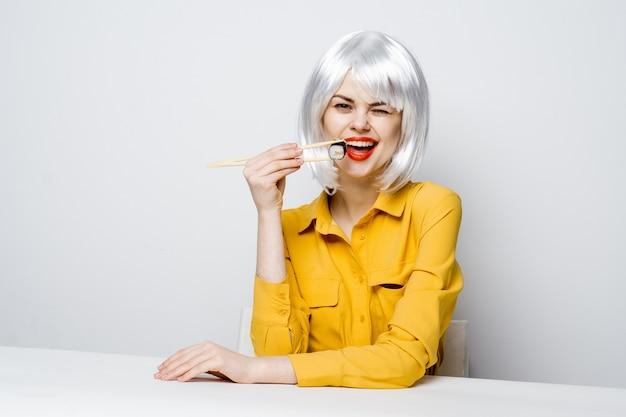 さまざまな感情のポーズをとって黄色のシャツのテーブルで寿司と食糧配達からのロールを食べる美しい女性モデル