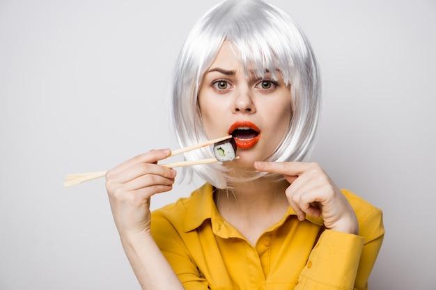 Красивая женщина-модель ест суши и роллы из службы доставки еды за столом в желтой рубашке, позирует с разными эмоциями