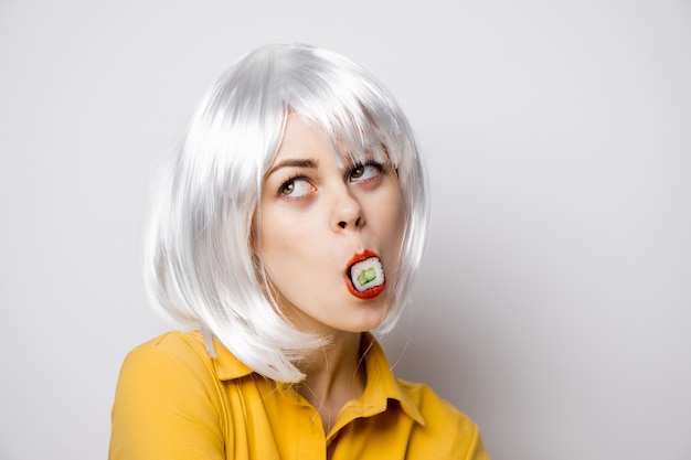 Beautiful woman model eating sushi and rolls from food delivery at the table in a yellow shirt posing different emotions