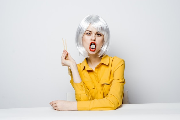 Beautiful woman model eating sushi and rolls from food delivery at the table in a yellow shirt posing