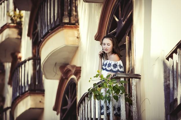 夏の古い建物のバルコニーでファッショナブルでセクシーな美しい女性モデル