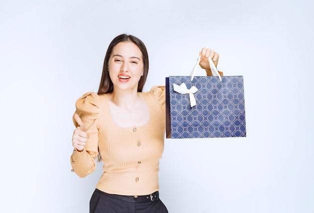 Un modello di bella donna che tiene una borsa della spesa con fiocco.