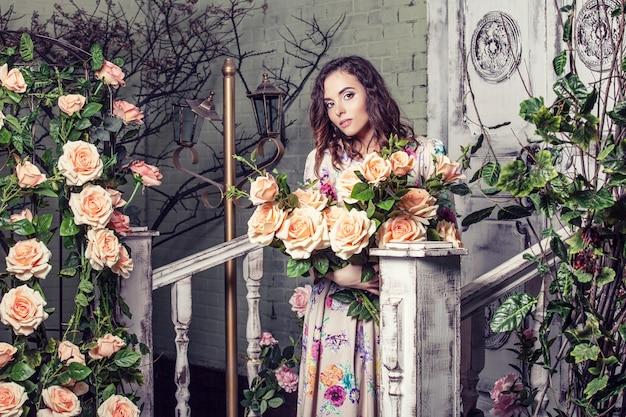 Модель красивая женщина в цветах роз в саду с красивым макияжем