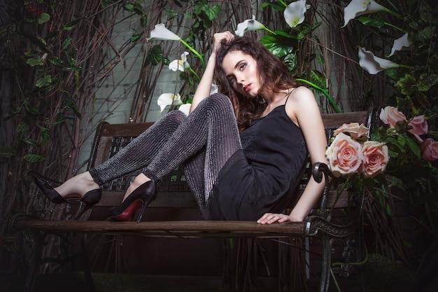 Модель красивой женщины в ночном саду в стильной черной тунике платья и леггинсах
