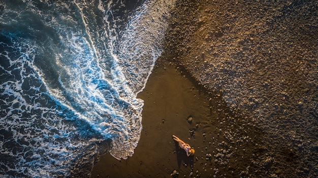 黒い火山のビーチに横になり、大きな波が来ている間に日光浴をしている美しい女性モデル。アウトドアの自然とライフスタイルのコンセプト。休暇と旅行の画像。航空写真。