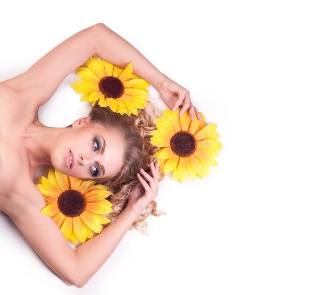 ひまわりの花の間に横たわる美しい女性モデル。スキンケアと健康的なライフスタイルのコンセプト