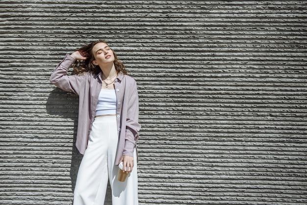 현대적인 세련된 옷 카탈로그에 여유 공간이 있는 도시 벽 배경에 포즈를 취한 아름다운 여성 모델